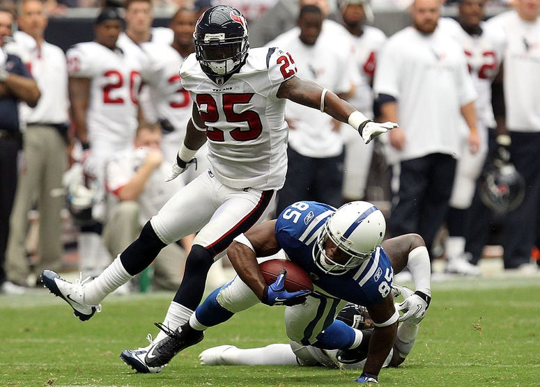 Wide receiver Pierre Garcon #85 of the Indianapolis Colts runs the ball against Zac Diles #54 and Kareem Jackson #25 of the Houston Texans during the NFL season opener at Reliant Stadium on September 12, 2010 in Houston, Texas.