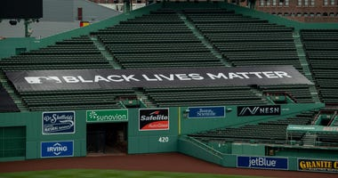 A Black Lives Matter tarp is displayed in the outfield bleacher seats before the start of the 2020 Major League Baseball season on July 23, 2020 at Fenway Park in Boston, Massachusetts. The season was delayed due to the coronavirus pandemic.