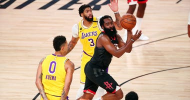 James Harden #13 of the Houston Rockets passes the ball against Kyle Kuzma #0 and Anthony Davis #3 of the Los Angeles Lakers in the second half at The Arena at ESPN Wide World Of Sports Complex on August 6, 2020 in Lake Buena Vista, Florida.