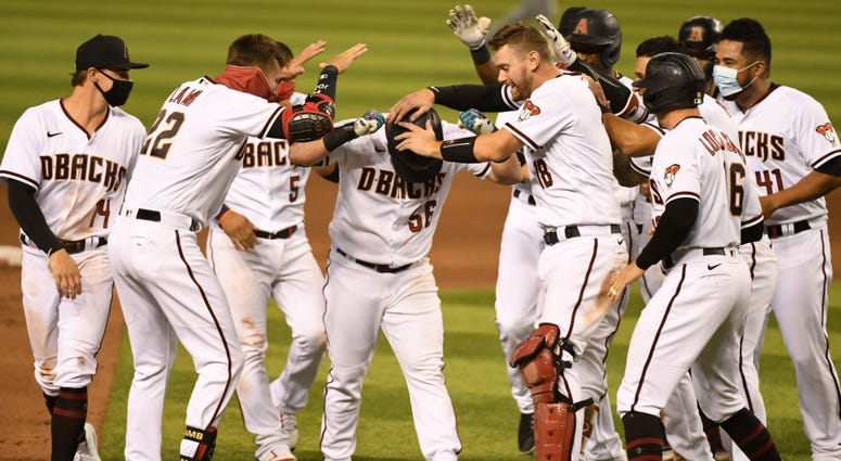 Kole Calhoun #56 of the Arizona Diamondbacks celebrates with Carson Kelly #18, Jake Lamb #22 and teammates after hitting a walk off two run single during the ninth inning for a 5-4 win against the Houston Astros at Chase Field on August 06, 2020.