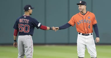 Mookie Betts #50 of the Boston Red Sox talks with George Springer #4 of the Houston Astros before game two of the American League Division Series at Minute Maid Park on October 6, 2017 in Houston, Texas.