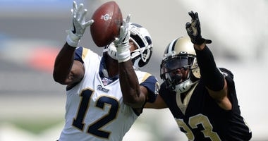 Los Angeles Rams wide receiver Brandin Cooks (12) catches a pass against New Orleans Saints cornerback Marshon Lattimore (23) during the first half at Los Angeles Memorial Coliseum.
