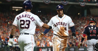 Houston Astros center fielder George Springer (4) celebrates with right fielder Michael Brantley (23) after scoring a run against the Washington Nationals in the first second in game six of the 2019 World Series at Minute Maid Park.