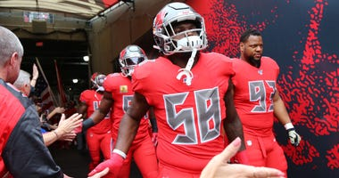 Tampa Bay Buccaneers linebacker Shaquil Barrett (58) and teammates run out of the tunnel prior to a game against the New Orleans Saints at Raymond James Stadium.