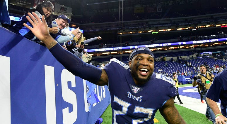 Tennessee Titans running back Derrick Henry (22) celebrates with fans after the Titans beat the Colts , 31-17, at Lucas Oil Stadium.