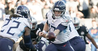 Tennessee Titans quarterback Ryan Tannehill (17) hands the ball off to running back Derrick Henry (22) against the Oakland Raiders during the third quarter at Oakland Coliseum.