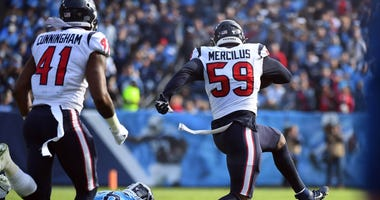 Houston Texans outside linebacker Whitney Mercilus (59) runs away from a tackle attempt from Tennessee Titans offensive guard Rodger Saffold (76) after an interception during the first half at Nissan Stadium.