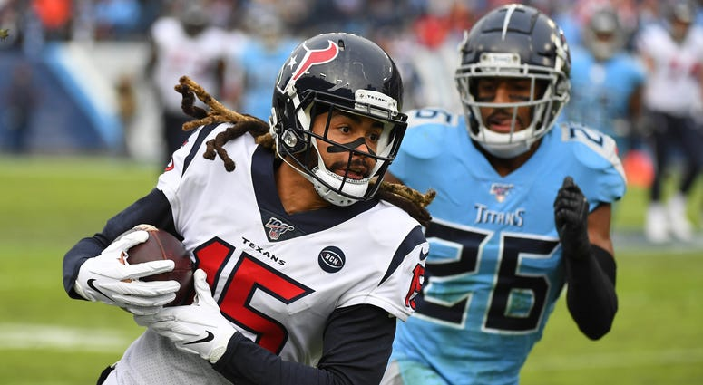 Houston Texans wide receiver Will Fuller (15) catches a pass past coverage fro Tennessee Titans cornerback Logan Ryan (26) during the second half at Nissan Stadium.