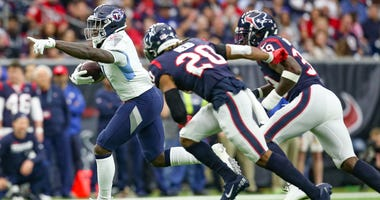 Tennessee Titans wide receiver A.J. Brown (11) points after catching the ball while Houston Texans strong safety Justin Reid (20) and free safety Tashaun Gipson (39) give chase in the first quarter at NRG Stadium.