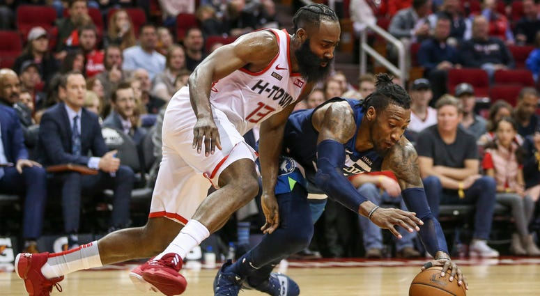 Houston Rockets guard James Harden (13) and Minnesota Timberwolves forward Robert Covington (33) attempt to get a loose ball during the second quarter at Toyota Center.