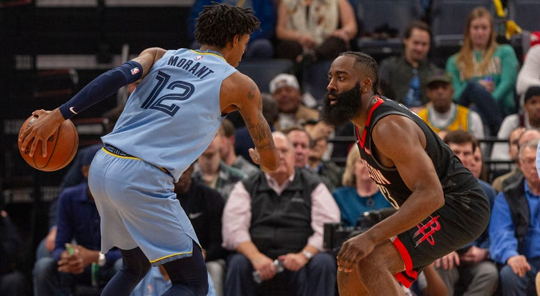 Memphis Grizzlies guard Ja Morant (12) handles the ball against Houston Rockets guard James Harden (13) during the first half at FedExForum.