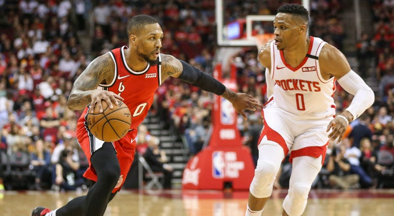 Portland Trail Blazers guard Damian Lillard (left) dribbles the ball against Houston Rockets guard Russell Westbrook (right) during the first quarter at Toyota Center.