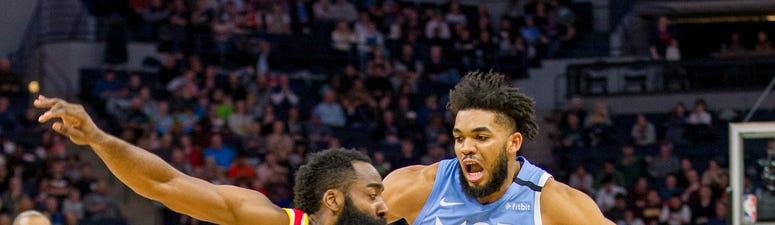 Minnesota Timberwolves center Karl-Anthony Towns (32) dribbles the ball behind his back as Houston Rockets guard James Harden (13) defends in the second half at Target Center.
