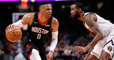 Houston Rockets guard Russell Westbrook (0) controls the ball as Denver Nuggets forward Will Barton III (5) guards in the fourth quarter at the Pepsi Center.