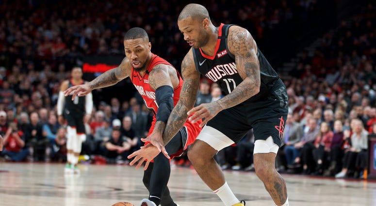 Portland Trail Blazers guard Damian Lillard (0) and Houston Rockets forward P.J. Tucker (17) reach for a loose ball during the first quarter at the Moda Center.