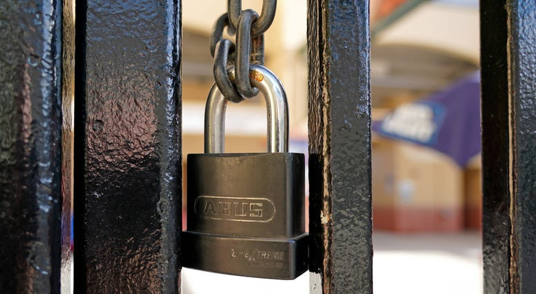 A padlock is seen on the gate of the entrance of Roger Dean Chevrolet Stadium. Major League Baseball has suspended the rest of its spring training schedule due to the Covid 19 coronavirus outbreak.