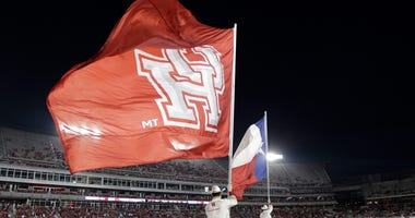 University of Houston Cougars Frontiersmen run with the Texas state flag and the U of H flag after a Cougar touchdown against the Southern Methodist University Mustangs at TDECU Stadium.