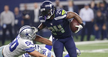, Dallas Cowboys outside linebacker Sean Lee (50) defends against a run by Seattle Seahawks running back Marshawn Lynch (24) during an NFL football game in Arlington, Texas.