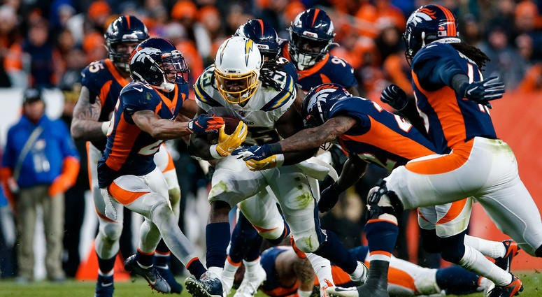 Los Angeles Chargers running back Melvin Gordon III (25) runs the ball under pressure from Denver Broncos cornerback Chris Harris Jr. (25), defensive end Derek Wolfe (95), inside linebacker Todd Davis.