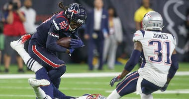 Houston Texans wide receiver DeAndre Hopkins (10) is tackled by New England Patriots cornerback Stephon Gilmore (24) in the second half at NRG Stadium.