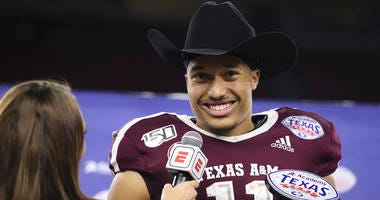 Texas A&M Aggies quarterback Kellen Mond (11) is handed the Texas Bowl MVP trophy after defeating the Oklahoma State Cowboys at NRG Stadium.