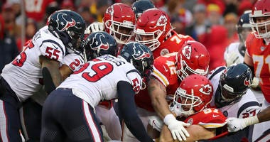Kansas City Chiefs tight end Travis Kelce (87) is gang tackled by the Houston Texans defense during the second half in a AFC Divisional Round playoff football game at Arrowhead Stadium.
