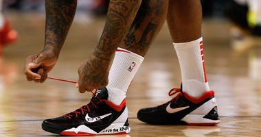 Houston Rockets forward P.J. Tucker (17) ties his shoes before the game against the Denver Nuggets the at the Pepsi Center. A tribute for former Lakers player Kobe Bryant is written on the shoes.