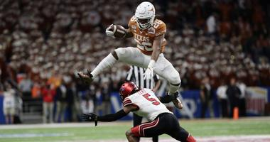 Texas running back Keaontay Ingram (26) leaps over Utah defensive back Tareke Lewis (5) during the second half of the Alamo Bowl NCAA college football game in San Antonio, Tuesday, Dec. 31, 2019.