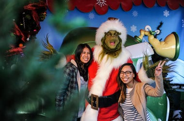 "A figure of ""Grinch"" poses for photos with tourists during the ""Grinchmas"" celebration at the Universal Studios Hollywood"