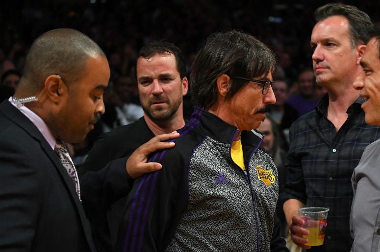 Anthony Kiedis, lead singer of the band Red Hot Chili Pepper, is escorted off the floor after he yelled profanities at Houston Rockets guard Chris Paul