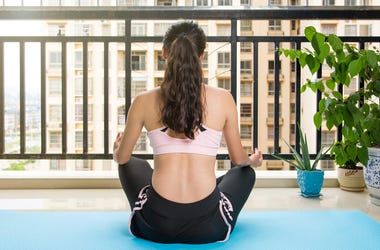 Girl meditating at the balcony on a yoga mat. Home workout