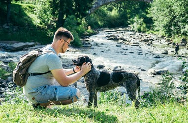 Young strong man stays near mountains river with dog and looking for the view. Fidelity, life.