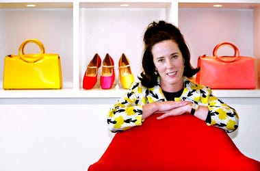 In this May 13, 2004 file photo, designer Kate Spade poses with handbags and shoes from her next collection in New York. Law enforcement officials say Tuesday, June 5, 2018, that New York fashion designer Kate Spade has been found dead in her apartment in