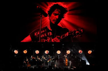 "Singer Ryan Adams performs with his band underneath an image of the late singer Chris Cornell during ""I Am The Highway: A Tribute to Chris Cornell"" at The Forum, Wednesday, Jan. 16, 2019, in Inglewood, Calif. (Photo by Chris Pizzello/Invision/AP)"