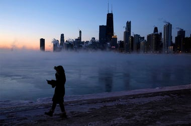A person walks along the lakeshore, Wednesday, Jan. 30, 2019, in Chicago. A deadly arctic deep freeze enveloped the Midwest with record-breaking temperatures on Wednesday, triggering widespread closures of schools and businesses, and prompting the U.S. Po