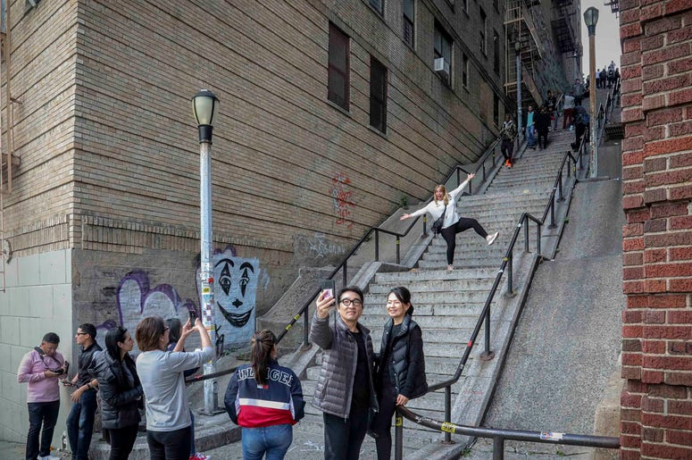 "People pose on the steps between two apartment buildings, Monday Oct. 28, 2019, in the Bronx borough of New York. The stairs have become a tourist attraction in recent weeks since the release of the movie ""Joker."" In the movie, lead actor Joaquin Phoenix"