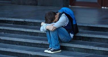 sad grade schooler on the steps