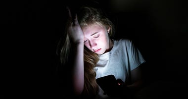 girl upset sitting in the dark with her phone