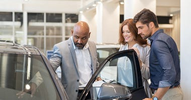 couple looking at a new car in a showroom