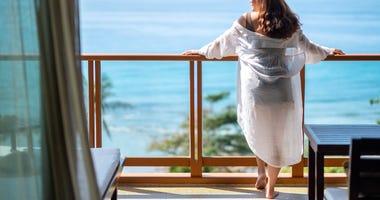 woman on a balcony overlooking a beach
