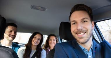 man driving three girls in a ride share car