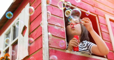 girl blowing bubbles in a play house