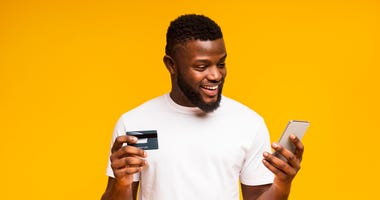 man smiling with a credit card