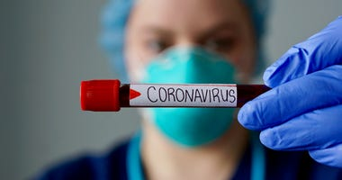medical mask and vial of blood with coronavirus label on it