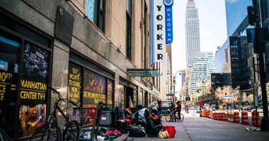 homeless people camping on a sidewalk, empire state building in the background