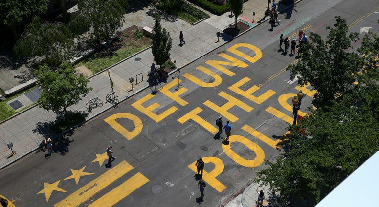 defund the police painted on a city street
