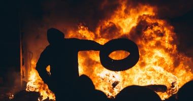 rioters fueling a fire with a tire