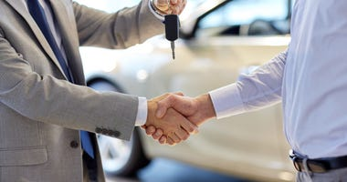 car salesman handing keys to new owner