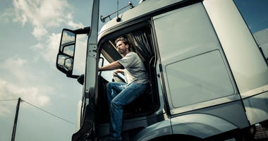 man climbing out of a truck cab