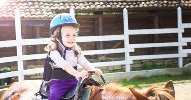 little girl riding a horse as equine therapy